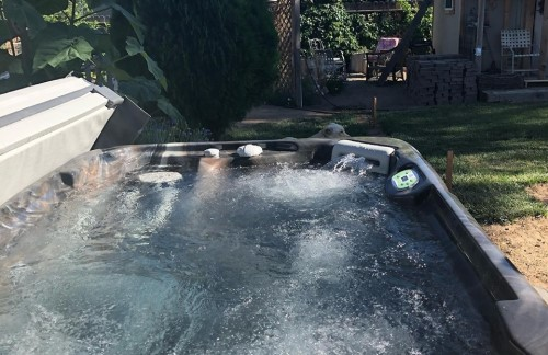 Hot tub for two people running in backyard.